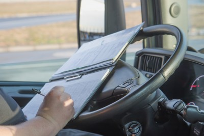 Image of truck driver completing his fatigue managmeent courses notes in a clip folder on his steering wheel