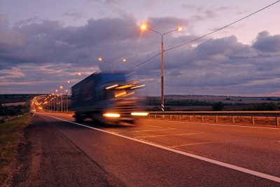 Image of a large truck driving at twilight (a fatigue management courses hazard period) using slow shutter photography