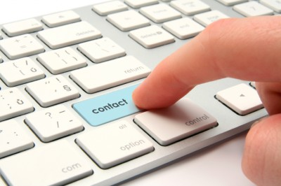 Stock image of finger on the Contact button of a keyboard