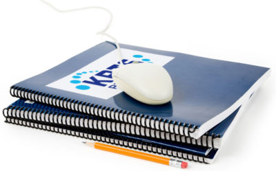 Image of a mouse on top of KRTS bound notebooks